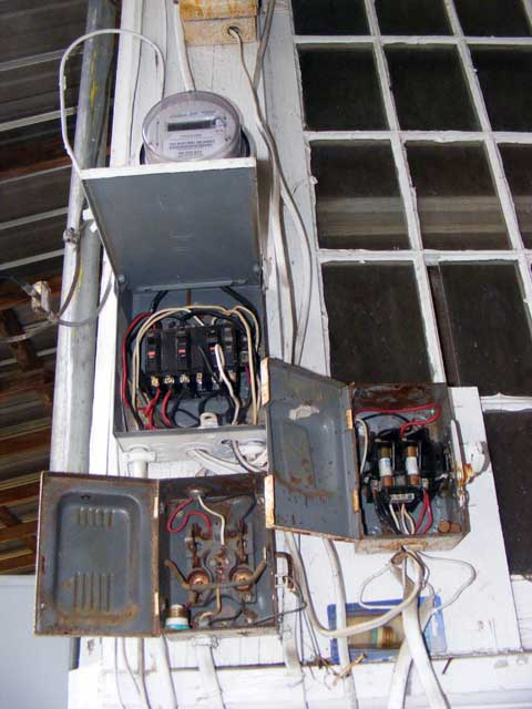 The existing service drop and fuse boxes in all their glory.